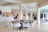 View of the kitchen and bar table in the main room of the Villa del Mar, facing the sea